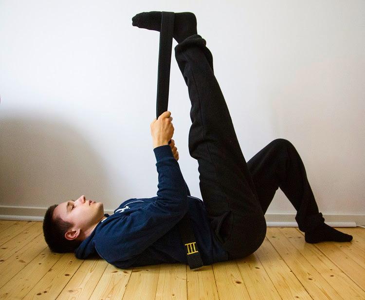 Reiden takaosan lihaksia on helppo venyttää aktiivisella kohdevenyttelyllä käyttäen apuna vyötä.